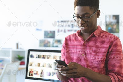 Front view of happy young African-American graphic designer using mobile phone at desk in office