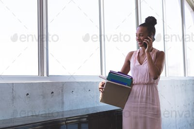 Young mixed-race businesswoman talking on mobile phone while holding stuffs in the modern office