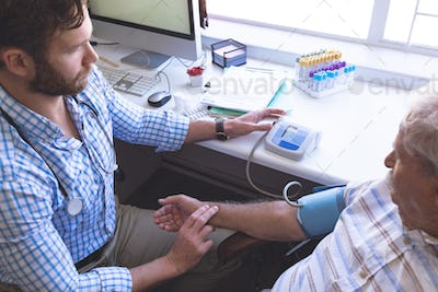 Caucasian male doctor checking blood pressure of senior patient with blood pressure gauge
