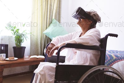 Side view of senior mixed race woman using virtual realty headset at nursing home
