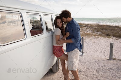 Side view of Caucasian Couple leaned on a camper van while they hugging themselves