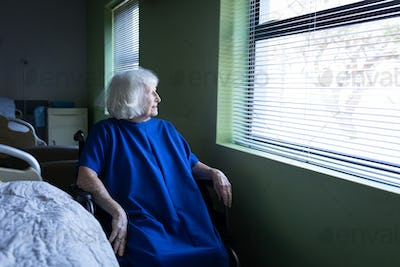 Senior Caucasian female patient looking outside through the window while sitting on a wheelchair