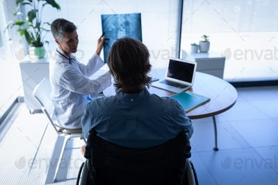 Mature Caucasian female doctor showing x-ray report to disabled patient in wheelchair in clinic
