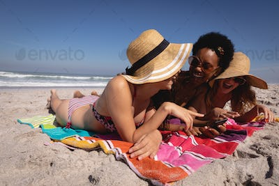 Happy beautiful young multi ethnic women lying and relaxing on a blanket at beach while having fun