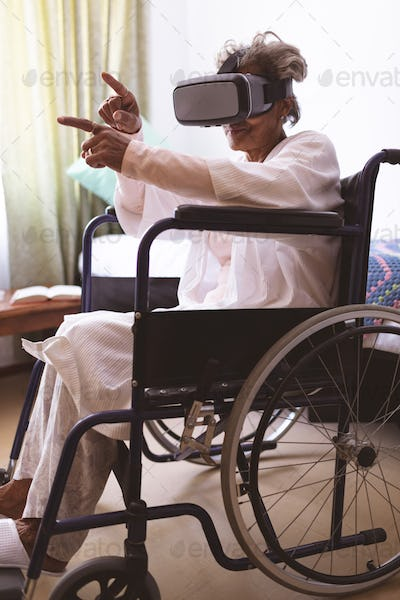Side view of senior mixed race  woman using virtual realty headset in wheelchair at nursing home