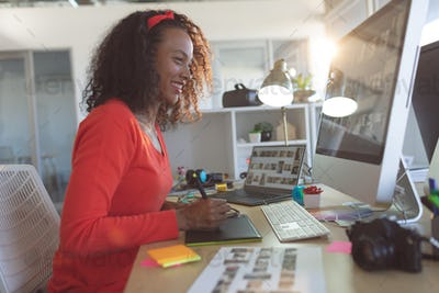 Happy young mixed-race female graphic designer using graphic tablet at desk in a modern office