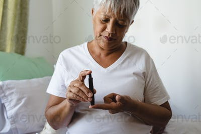 Mixed race female senior patient checking blood sugar level with glucometer at retirement home