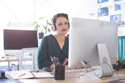 Front view of beautiful Mixed-race female executive working on computer at desk in the office