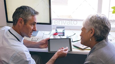 Male doctor discussing over digital tablet with senior woman at retirement home