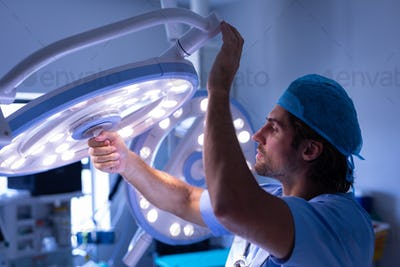 Side view of a Caucasian male surgeon fixing surgical light at hospital