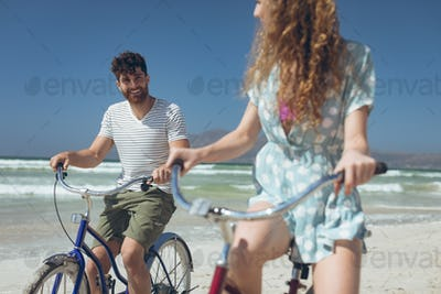 Couple riding bicycle at beach