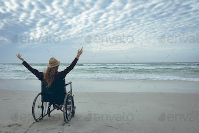 Young disabled woman sitting with arms in the air in wheelchair at beach