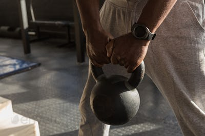 Senior man exercising with kettle bells standing in the fitness studio