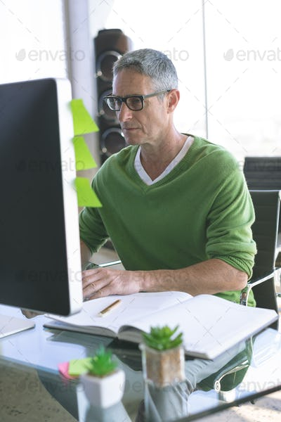 Front view of Caucasian businessman working on computer at desk in modern office