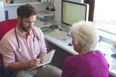 Male doctor writing prescription on notebook for senior woman in clinic room