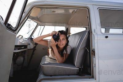 Woman capturing photo with digital camera in camper van at beach