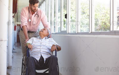 Male doctor and senior man talking with each other while doctor pushing his wheelchair