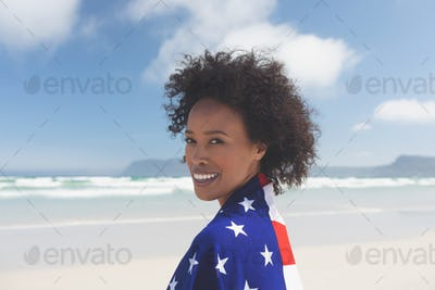 Woman wrapped in american flag at beach on a sunny day