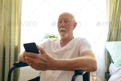 Front view of senior Caucasian male patient using mobile phone at retirement home