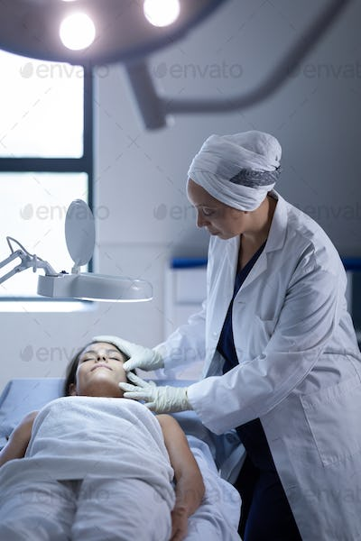 Mature female surgeon examining her patient during a plastic surgery in clinic