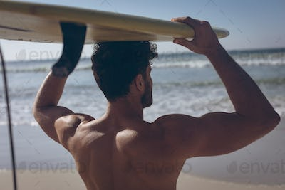 Rear view of young Caucasian male surfer carrying surfboard on his head at beach on sunny day
