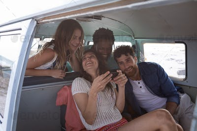 Group of friends interacting with each others in a camper van at beach