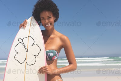 Happy female surfer with a surfboard standing on a beach on a sunny day