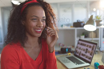 Front view of happy young mixed-race female executive talking on headset at desk in a modern office