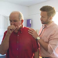 Male Caucasian doctor examining a senior patient thanks to a stethoscope while he is coughing