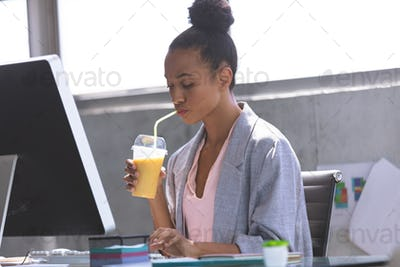 Young businesswoman having milkshake while working on computer at desk
