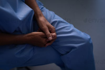 High angle view of a surgeon sitting with hand clasped and legs crossed  at hospital