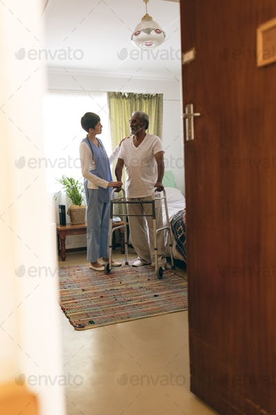 Female nurse talking with senior man while walking with walker at retirement home