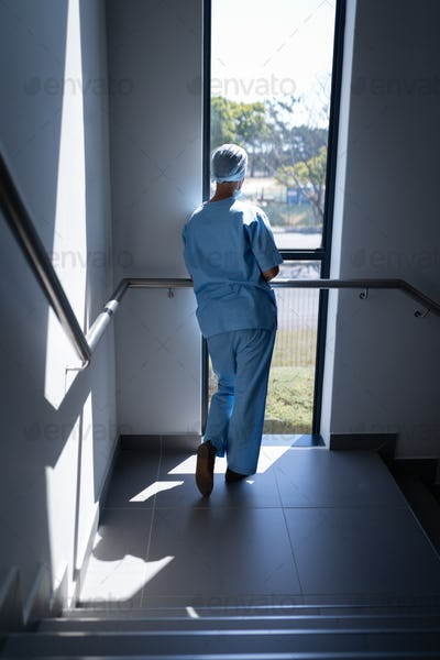 Rear view of a female surgeon looking through the window while standing in the hospital stairs