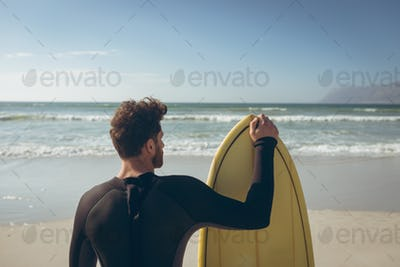 Rear view of young Caucasian male surfer with a surfboard standing on a beach on sunny day