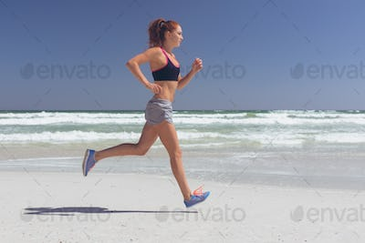 Side view of beautiful young  Caucasian fit woman running at beach on a sunny day