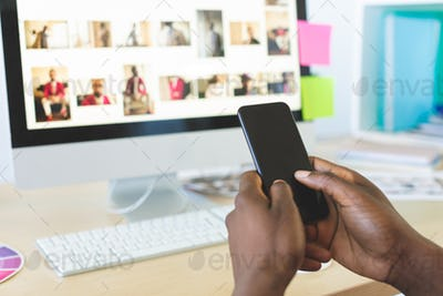 Rear view of young African-American graphic designer using mobile phone at desk in office