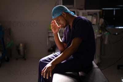 Nervous  male surgeon sitting with his head in his hand in operation room at hospital