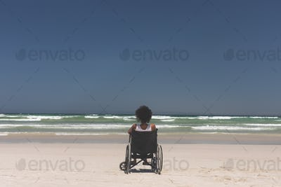 Young woman disable sitting on wheelchair at beach on a sunny day
