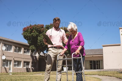 Male doctor helping senior woman with her walker at backyard nursing home
