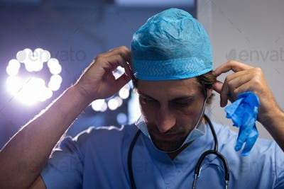 Male surgeon putting on his surgery hat and getting ready for the operation at hospital