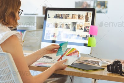 Rear view of young Caucasian graphic designer checks the color with color swatch at desk in office