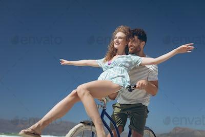 Couple enjoying on bicycle at beach