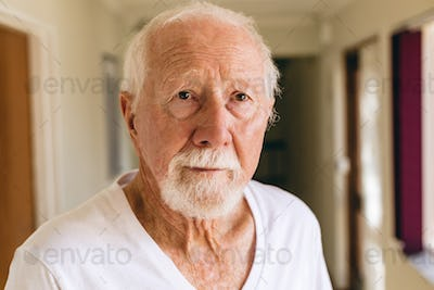 Front view of senior Caucasian male patient standing in corridor at retirement home