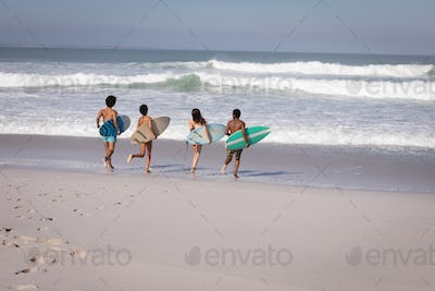 Group friends running to the waterside with surfboards while having fun at beach