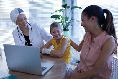 Female doctor and mother talking with girl patient in clinic at hospital
