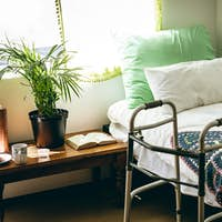 Front view of empty bed and walker in bed room at retirement home