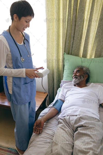 Female nurse checking blood pressure of senior male patient at retirement home