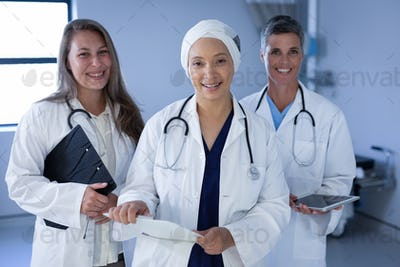 Female doctors standing in the hospital with stethoscope around the neck while holding folder
