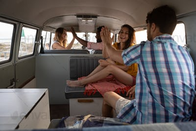 Rear view of a group of multi-ethnic friends giving high five in camper van at beach on a sunny day