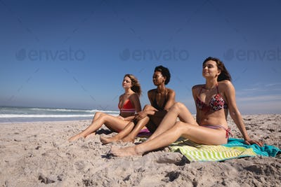 Women relaxing on blankets at beach
